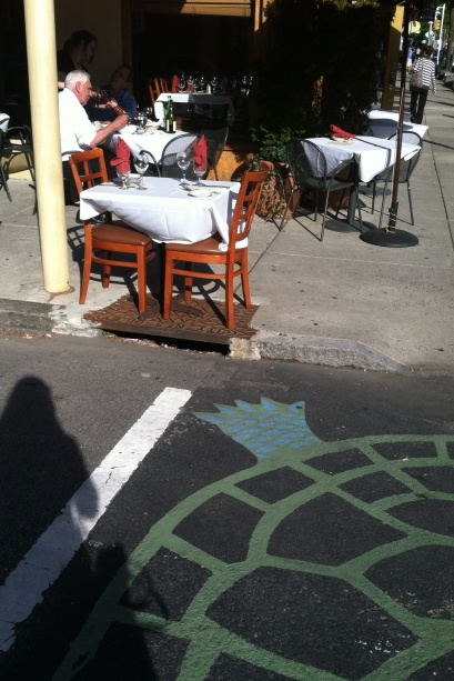 This curbside table is right over a storm drain and very close to the crosswalk.
